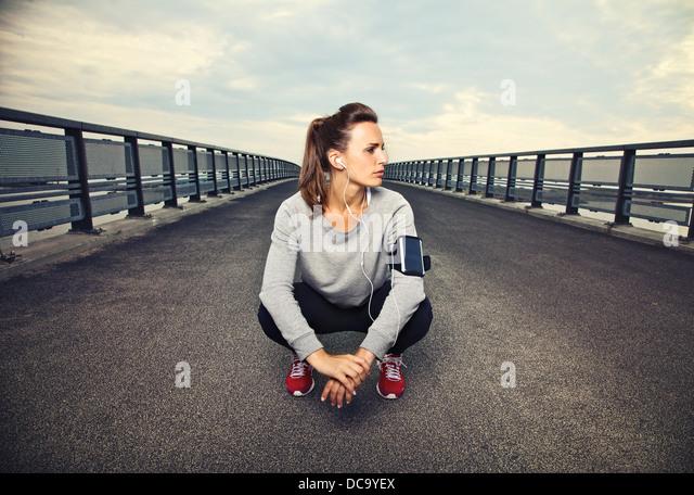 Weibliche Läufer sitzt auf der Brücke nach laufen Stockbild