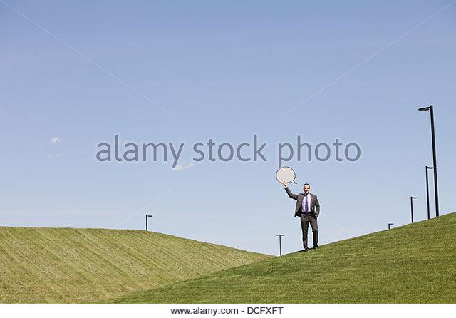 Geschäftsmann mit Sprechblase auf Hügel Stockbild
