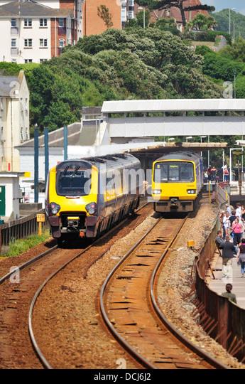 Ein Crosscountry express Personenzug übergibt ein First Great Western regional Nahverkehrszug in Dawlish Station Stockbild