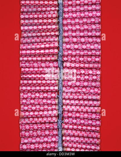 Eine Reihe von roten Feuerwerkskörper statt durch eine Sicherung. Leuchtend roten Hintergrund Stockbild