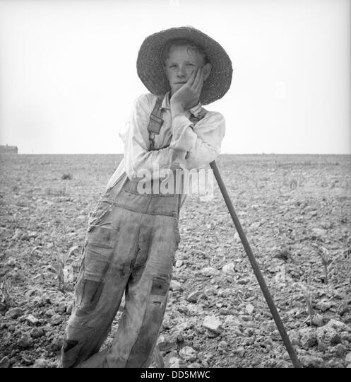 Arme weiße Bauernjunge stützte sich auf seine Hacke in North Carolina. Juli 1936. Foto von Dorothea Lange. Stockbild