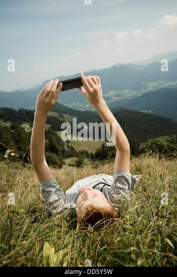 Deutschland, Bayern, junge, wieder in Bergen liegend verwendet ein smart phone Stockbild
