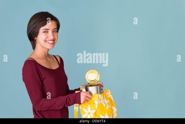 Porträt von lächelnden jungen multirassische Frau recycling Metall Dosen Stockbild