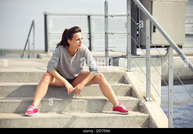 Sportlerin, die sitzt auf der Treppe eine Pause vom laufen Stockbild
