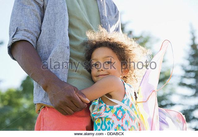 Porträt der niedliche Mädchen umarmen Vater im park Stockbild