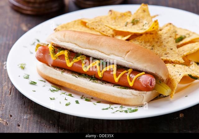 Hot Dog mit Senf und Kartoffel-Chips auf hölzernen Hintergrund Stockbild