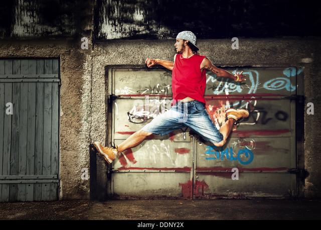 Junger Mann / Jugendliche springen / Tanz auf Grunge-Graffiti-Wand-Hintergrund Stockbild