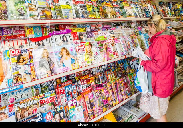 Sieht eine Frau in ihr 30 Zeitschriften zu verkaufen in Zeitschriftenläden im Vereinigten Königreich Stockbild