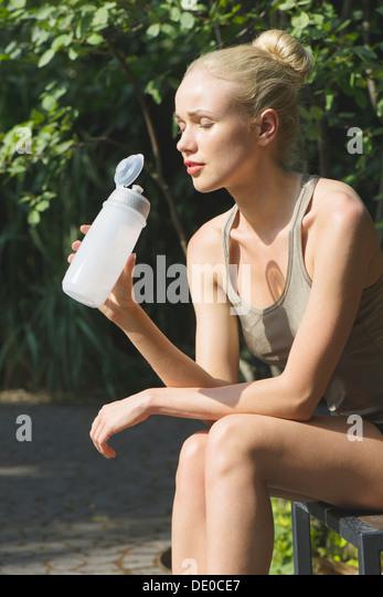 Junge Frau sitzt im Freien mit Wasserflasche, Augen geschlossen Stockbild