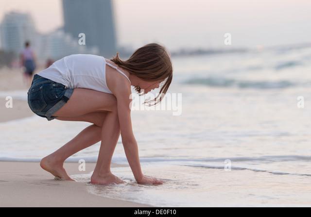 Mädchen spielen mit Wasser am Strand Stockbild