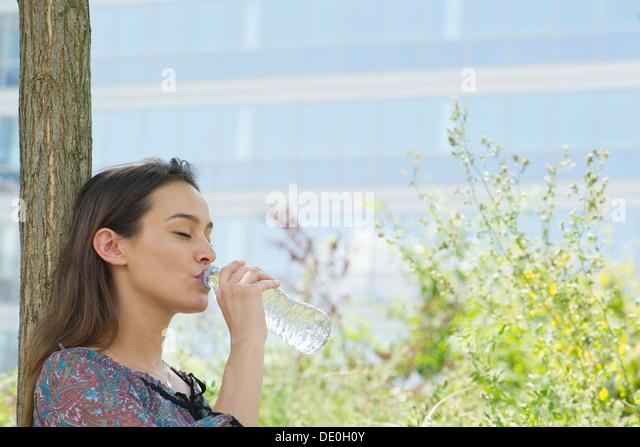 Frau trinkt Mineralwasser im freien Stockbild