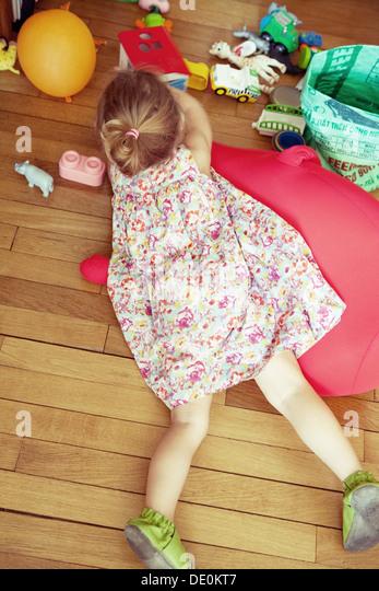 Kleines Mädchen am Boden liegend, mit Spielzeugen, Draufsicht Stockbild