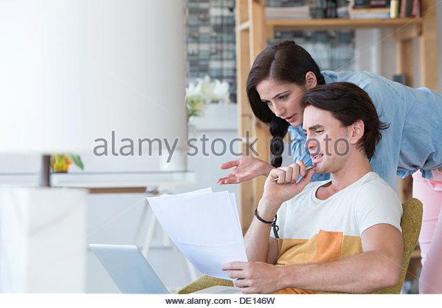 Ernst paar blickte auf Papierkram und laptop Stockbild