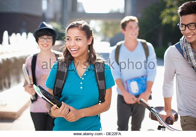 Studenten, die zusammen im Freien spazieren Stockbild