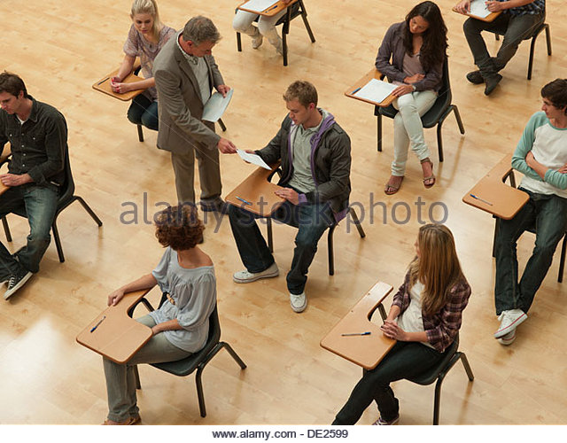 Professor verteilen Antwortbogen im Klassenzimmer Stockbild