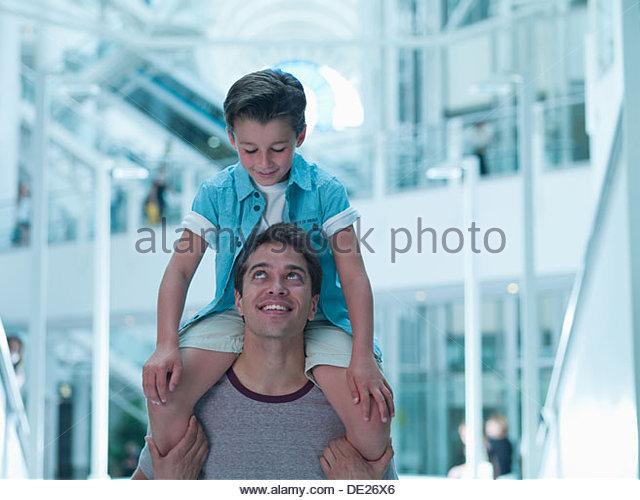Vater mit Sohn auf Schultern in der mall Stockbild