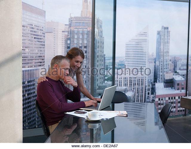 Paar auf Computer mit Stadtbild im Hintergrund arbeiten Stockbild