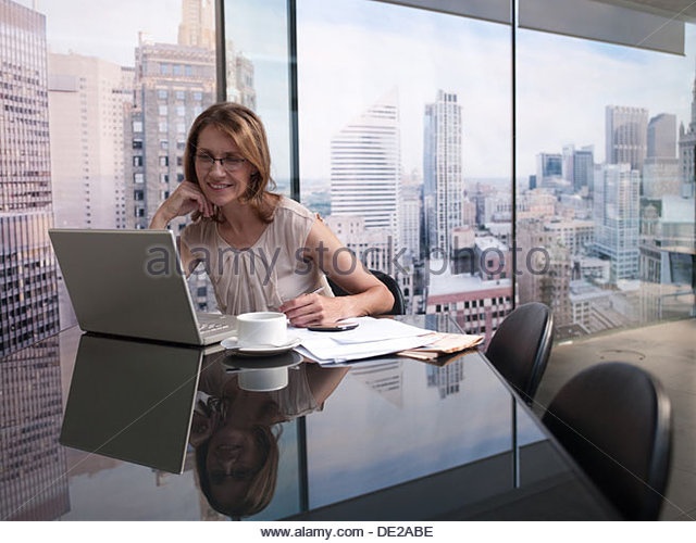 Frau, die auf Computer mit Stadtbild im Hintergrund Stockbild