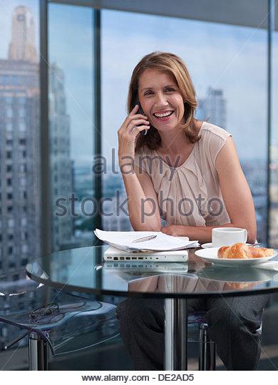 Frau am Telefon mit Stadtansicht im Hintergrund Stockbild