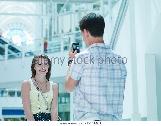 Menschen nehmen Foto der Freundin im Einkaufszentrum Stockbild