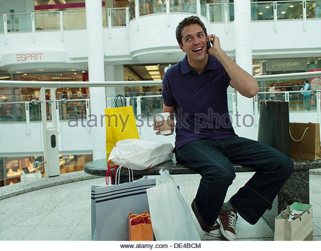 Lächelnd Mann im Einkaufszentrum sprechen auf Handy Stockbild