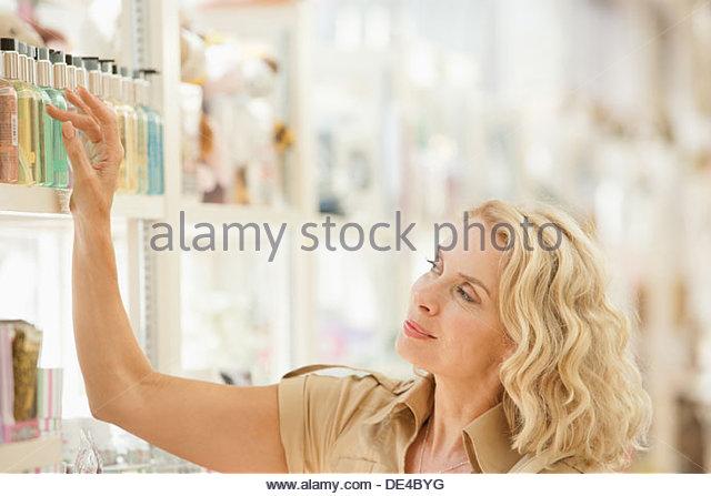 Lächelnde Frau Griff nach Parfüm auf Regal Stockbild