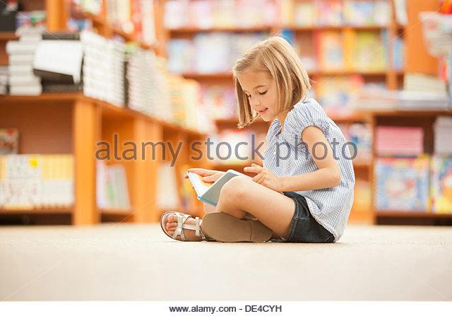 Mädchen sitzen auf dem Boden der Bibliothek mit Buch Stockbild