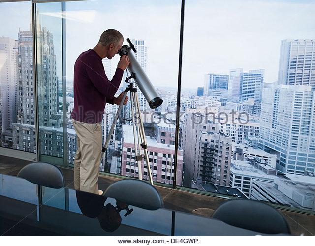 Mann mit Teleskop um zu betrachten Gebäude der Stadt Stockbild