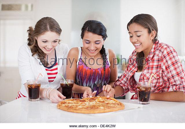 Mädchen im Teenageralter Pizza essen Stockbild