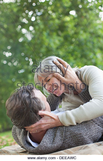 Paar Handauflegen Decke im park Stockbild