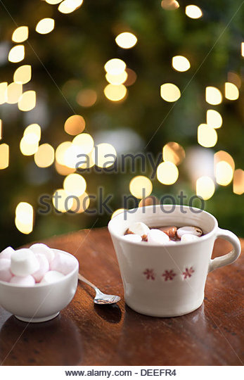 Tasse heißen Kakao, Weihnachtsbaum im Hintergrund Stockbild