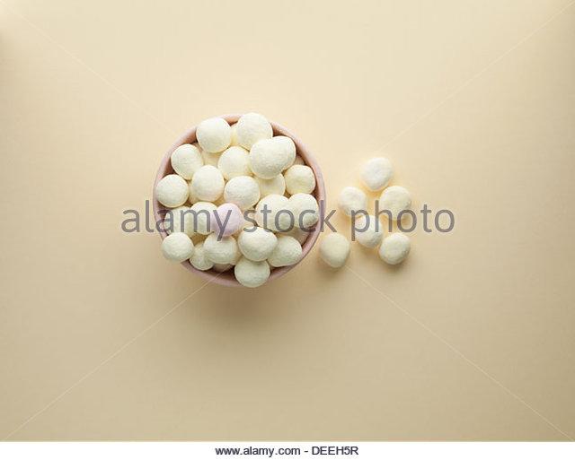 Schale mit weißen Bon Bons und ein rosa Minze Stockbild