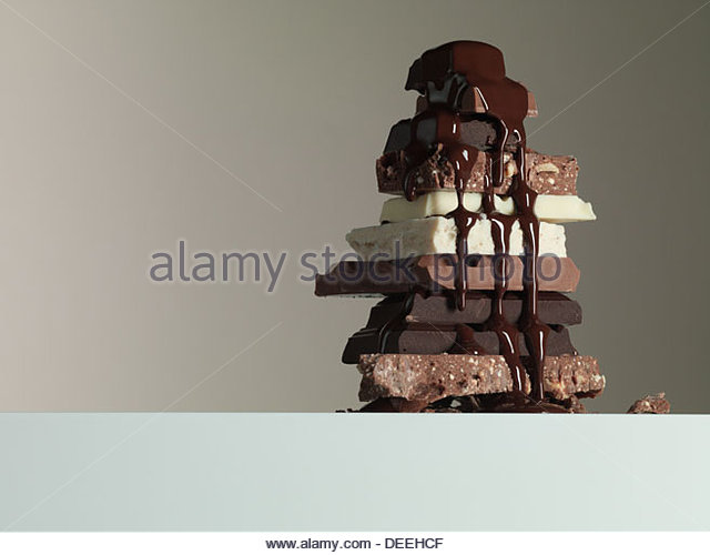Schokoladensirup tropft über Stapel von Tafeln Schokolade Stockbild