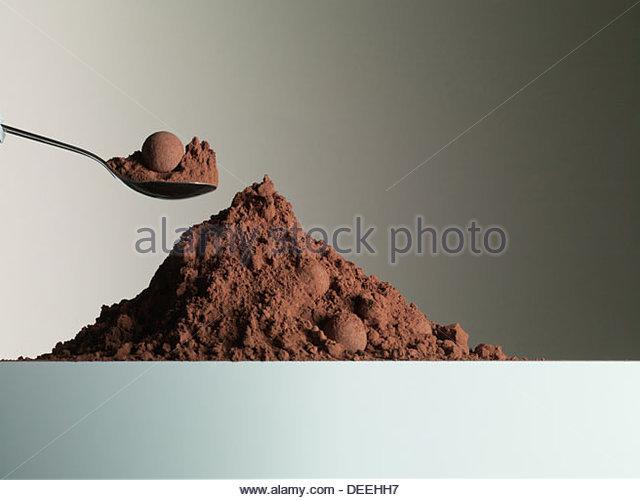 Löffel in Haufen von Kakaopulver Stockbild