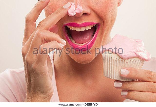 Frau mit rosa Lippenstift und Zuckerguss auf Nase Cupcake Essen Stockbild