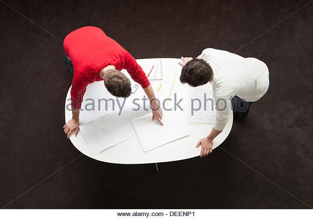 Zwei Geschäftsleute, beugte sich über einen Tisch mit Entwürfen und Papierkram Stockbild