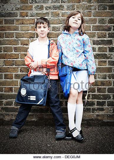 Jungen und Mädchen stehen vor der Ziegelwand mit Schultaschen Stockbild