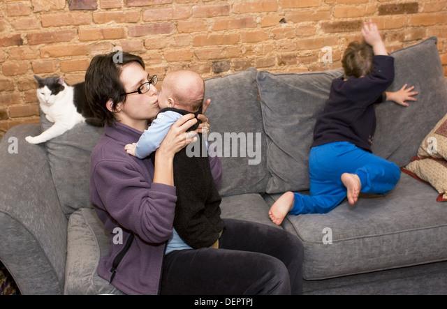 Mutter mit drei - Jahr - alten und drei - Monat - alte auf der Couch mit Katze auf. Stockbild