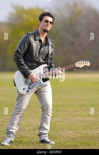 junge Rock-Musiker spielt e-Gitarre im freien Stockbild