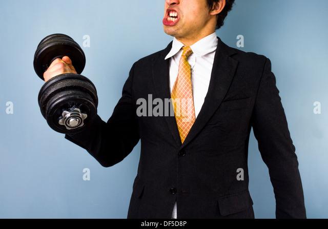 Starke Geschäftsmann arbeitet und mit einer Hantel trainieren Stockbild