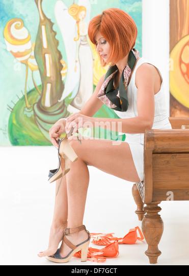 Seitenansicht der junge schöne rothaarige Frau sitzt auf einer Holzbank, die ihre Schuhe mit bunten Bildern Stockbild