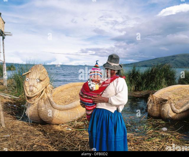 Uru indische Mutter und Kind und Totora-Schilf Boot. Titicaca-See. Peru Stockbild