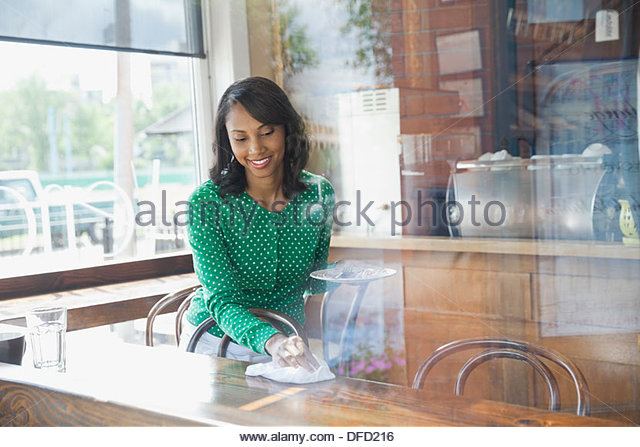 Lächelnd Kellnerin Reinigung Tisch im café Stockbild