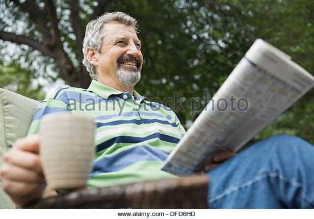Happy senior woman mit Kaffeetasse und Zeitung sitzen auf Hof Stockbild