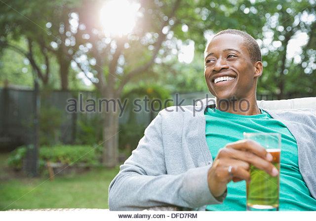 Lächelnder Mann entspannen bei einem Drink im Hinterhof Stockbild