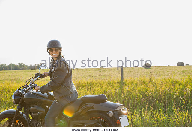 Porträt von weiblichen Biker auf dem Motorrad sitzen Stockbild