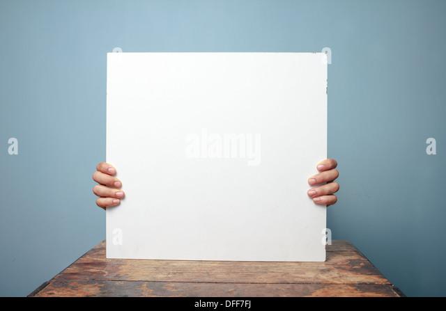 Junger Mann an einem Tisch sitzen und halten ein leeres weißes Schild, nur seine Finger sichtbar sind Stockbild