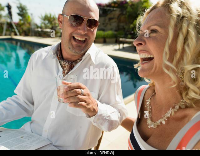 Ein junger Mann genießt sein Getränk mit einer schönen Frau an der Seite eines Schwimmbades in San Stockbild