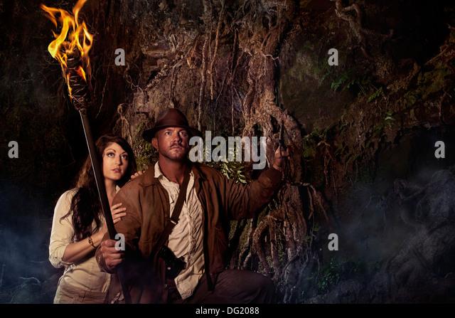 Indiana Jones Abenteuer Jäger in Höhle mit Frau Fackel gestylt Stockbild