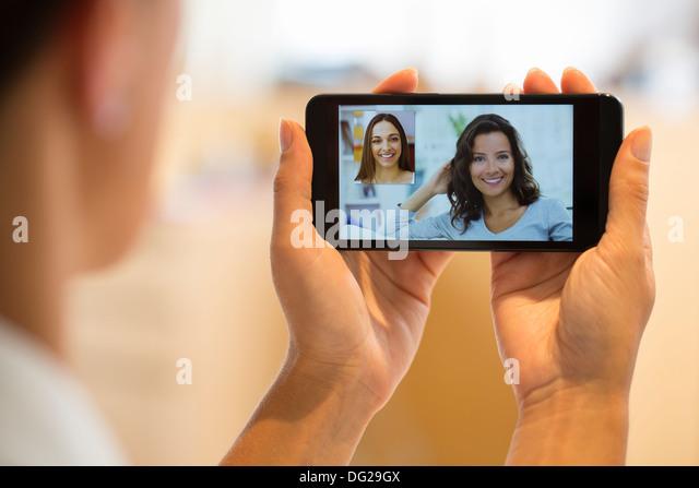 Frau mit ihrer Freundin auf Smartphone chatten Stockbild